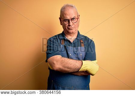 Middle age cleaner man cleaning wearing apron and gloves over isolated yellow background skeptic and nervous, disapproving expression on face with crossed arms. Negative person.