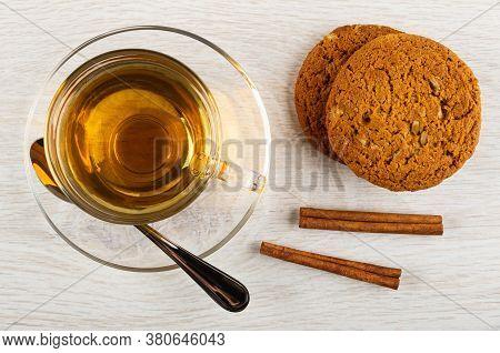 Cup Of Tea, Teaspoon In Transparent Saucer, Oat Cookies With Sunflower Seeds, Cinnamon Sticks On Woo
