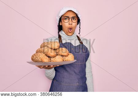 Young african american baker woman wearing apron holding wholemeal bread with cereal scared in shock with a surprise face, afraid and excited with fear expression