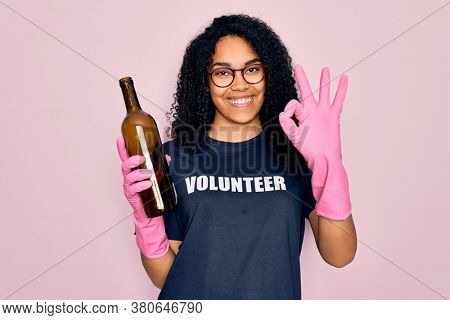 African american curly woman wearing volunteer t-shirt doing volunteering recycling glass bottle doing ok sign with fingers, excellent symbol