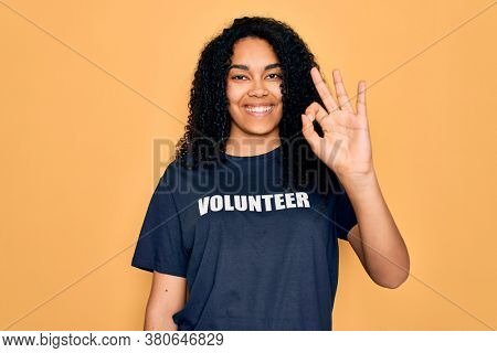 Young african american curly woman doing volunteering wearing volunteer t-shirt doing ok sign with fingers, excellent symbol