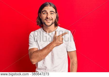 Young handsome man wearing casual clothes cheerful with a smile of face pointing with hand and finger up to the side with happy and natural expression on face