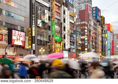Shinjuku, Tokyo, Japan - April 16, 2010:  People With Umbrellas Under The Rain In The Bustling Neigh