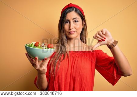 Young beautiful brunette woman eating healthy salad over isolated yellow background with angry face, negative sign showing dislike with thumbs down, rejection concept