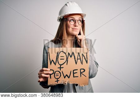 Young redhead architect asking for women rights holding banner with woman power message serious face thinking about question, very confused idea
