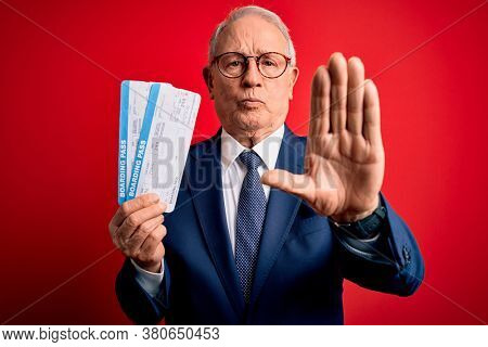 Senior grey haired business man holding airplane boarding pass over red background with open hand doing stop sign with serious and confident expression, defense gesture