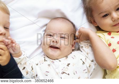 Little Smiling Kids Playing Together Sitting On The Bed. Brother And Sister Show A Newborn A Toy. To