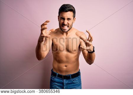 Young handsome strong man with beard shirtless standing over isolated pink background Shouting frustrated with rage, hands trying to strangle, yelling mad