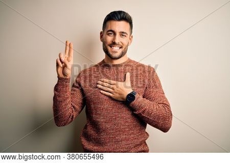 Young handsome man wearing casual sweater standing over isolated white background smiling swearing with hand on chest and fingers up, making a loyalty promise oath