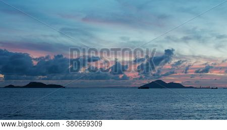 Sea and sky with island at sunset