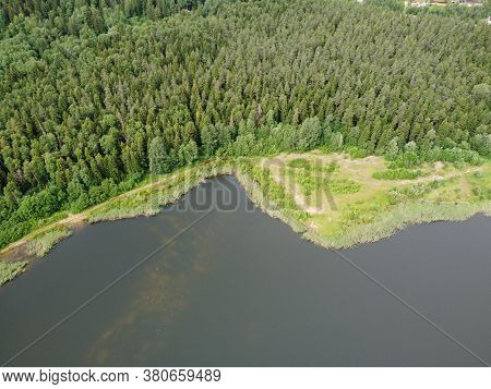 Woodland On The Shore Of A Reservoir On A Summer Day Aerial Photo.