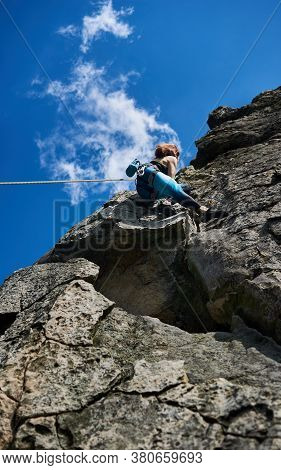 Low Angle View. Female Mountaineer In Sportswear Climbing Alpine Ridge Under Beautiful Cloudy Sky, A