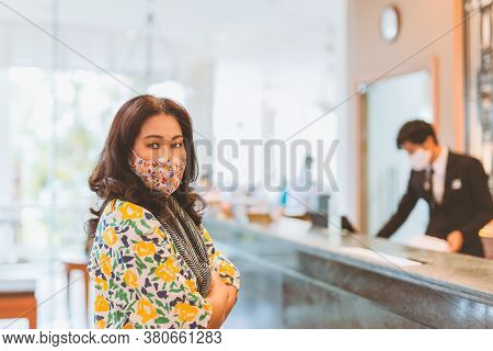 Woman Check In At Reception Counter In Hotel Wearing Medical Mask.