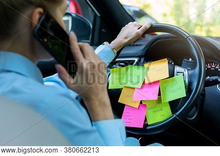 Busy Day Schedule Concept - Woman Driving Car With To Do List Notes On The Wheel And Talking On The