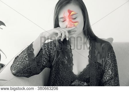 Asian Women In Satin Purple Nightgown Feeling Unwell And Sinus Against A Gray Background. Dust Aller