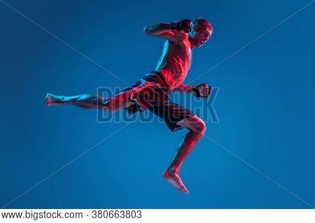 High Flight. Mma. Professional Fighter Punching Or Boxing Isolated On Blue Studio Background In Neon