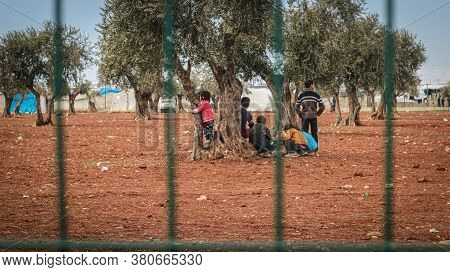 Idlib, Syria January 14, 2019:\nrefugee Tents Are Spread Among The Trees, Refugee Children Play Amon