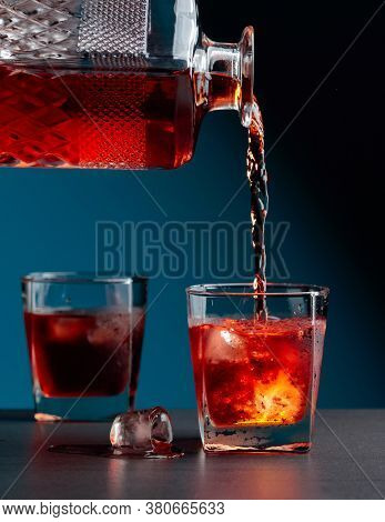 Whiskey Pours Into A Steamed Glass With Natural Ice. Alcoholic Drink Is Poured From A Crystal Decant