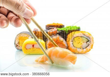 Wooden Chopsticks That Handle Japanese Food, Salmon Rolls, Avocado Rolls And Various Views About Rai