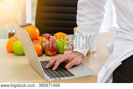 Doctor Nutritionist In White Lab Coat At Work, Sitting On Wooden Desk And Typing Dietary Consultatio