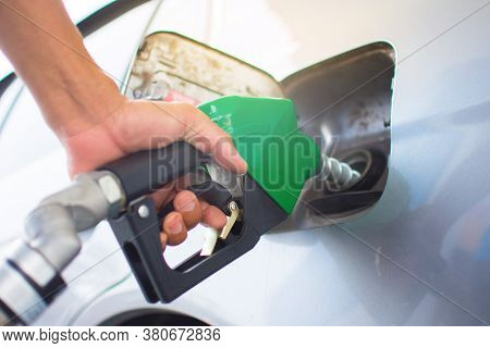 Close-up, Refueling Cars At The Fuel Pump Employees Hand To Refuel And Pump The Gasoline Of The Car