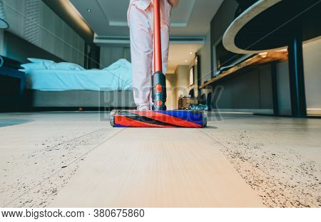Modern Vacuum Cleaner While Vacuuming. Woman Using A Vacuum Cleaner While Cleaning Carpet In The Hou