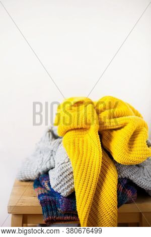 Pile Colorful Knitted Wool Clothes Or Sweaters On Wooden Table And White Wall Indoor Close-up With C