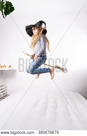 Schoolgirl In A Witch Hat Jumps On A Mattress And Flies On A Broomstick. Childrens Lifestyle Portrai