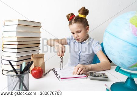 Back To School: A Girl Sits At Her Desk And Draws In A Notebook With The Help Of A Compass.