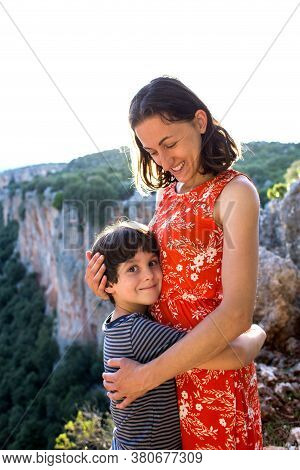 Portrait Of A Smiling Boy Hugging Mom, A Woman With A Child On Top Of A Mountain, A Child Congratula