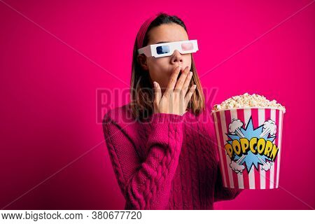 Young beautiful girl watching movie using 3d glasses eating box with popcorns bored yawning tired covering mouth with hand. Restless and sleepiness.