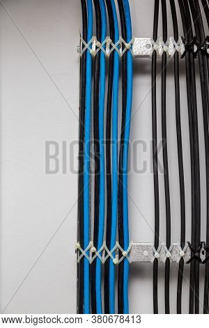 The Black And Blue Cable Wires Are Symmetrically Secured With White Cable Ties To The Metal Cable Tr