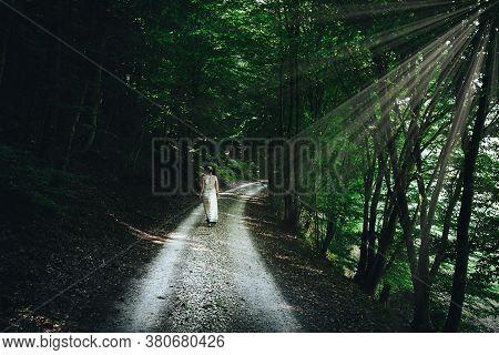 Blonde Caucasian Woman In Summer Dress Walking On Narrow Gravel Road Through Dark Forest