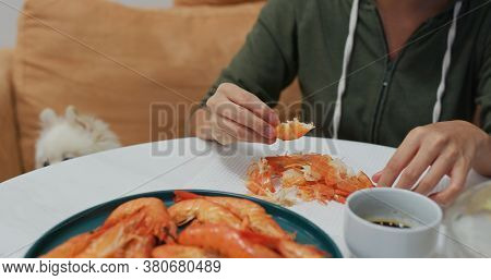 Woman eat shrimp with her dog sit aside at home