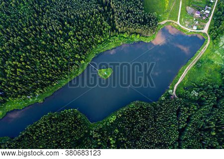 Aerial top down view of the pond in coniferous forest with little island in the middle