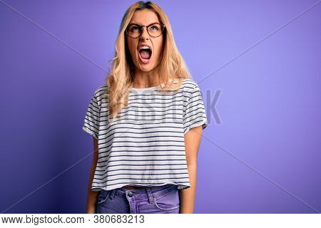 Young beautiful blonde woman wearing striped t-shirt and glasses over purple background angry and mad screaming frustrated and furious, shouting with anger. Rage and aggressive concept.