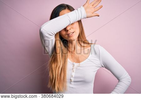 Young beautiful blonde woman with blue eyes wearing white t-shirt over pink background covering eyes with arm, looking serious and sad. Sightless, hiding and rejection concept