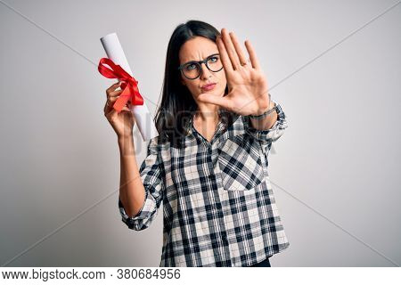 Young brunette student woman with blue eyes holding university diploma over isolated background with open hand doing stop sign with serious and confident expression, defense gesture