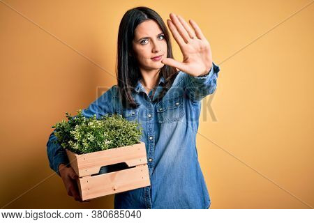 Young brunette woman with blue eyes holding wood box garden of fresh natural plants with open hand doing stop sign with serious and confident expression, defense gesture