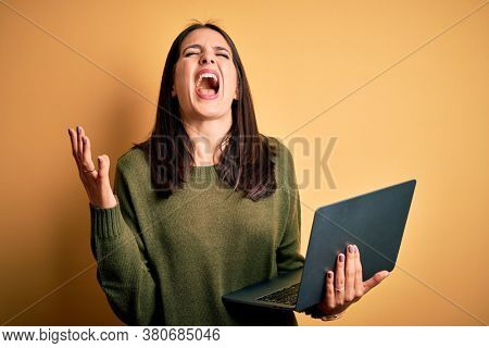 Young brunette woman with blue eyes working using computer laptop over yellow background crazy and mad shouting and yelling with aggressive expression and arms raised. Frustration concept.
