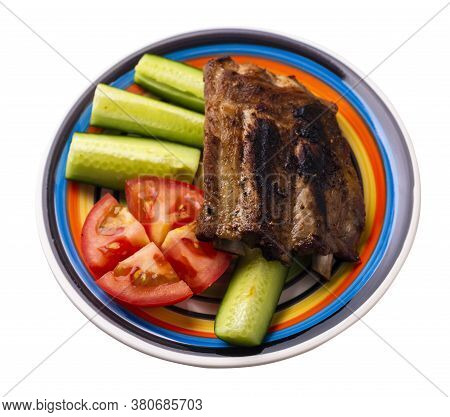 Grilled Pork Ribs With Sliced Cucumbers And Tomatoes On White Black Blue Red Yellow Plate. Pork Ribs