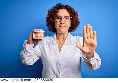 Middle age dentist woman wearing coat holding plastic denture teeth over blue background with open hand doing stop sign with serious and confident expression, defense gesture