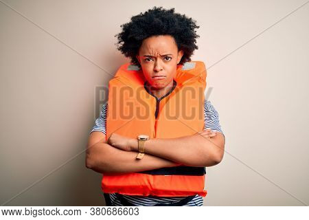 Young African American afro woman with curly hair wearing orange protection lifejacket skeptic and nervous, disapproving expression on face with crossed arms. Negative person.