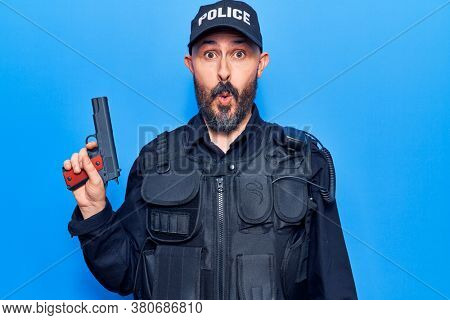 Young handsome man wearing police uniform holding gun scared and amazed with open mouth for surprise, disbelief face