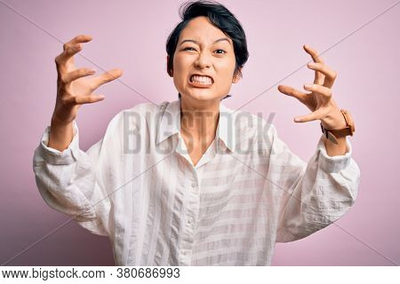 Young beautiful asian girl wearing casual shirt standing over isolated pink background Shouting frustrated with rage, hands trying to strangle, yelling mad