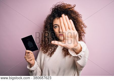 Beautiful tourist woman with curly hair and piercing holding canada canadian passport id with open hand doing stop sign with serious and confident expression, defense gesture