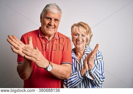 Senior beautiful couple standing together over isolated white background clapping and applauding happy and joyful, smiling proud hands together