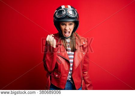 Young beautiful brunette motocyclist woman wearing motorcycle helmet and red jacket angry and mad raising fist frustrated and furious while shouting with anger. Rage and aggressive concept.