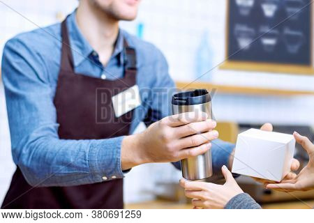 Barista Man In Brown Apron Is Giving Packed Order To Woman. Guy Made Coffee To Go In Metal Reusable