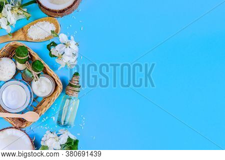 Cosmetics Jars, Bottles With Coconut Oils, Creams Are Laid Out On Left Side Of Blue Background. Summ